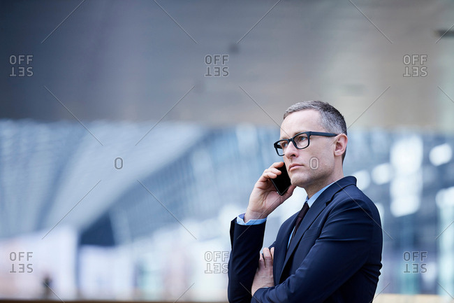 Stressed businessman making smartphone call in office atrium
