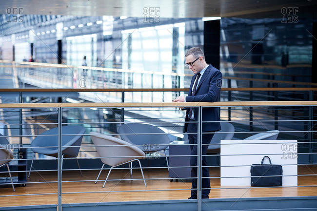 Businessman looking at smartphone on office balcony