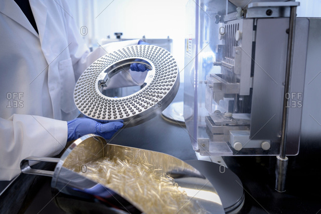 Operator using capsule filling machine in pharmaceutical factory