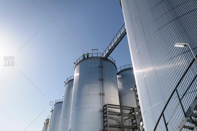 Worker on top of storage tanks in oil blending factory