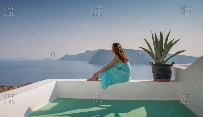 Woman on terrace looking away at view of sea, Santorini, Cyclades, Greece