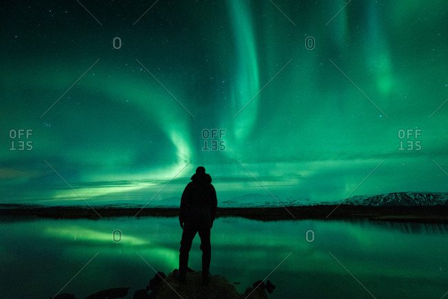 Man looking away at aurora borealis, Thingvellir, Iceland