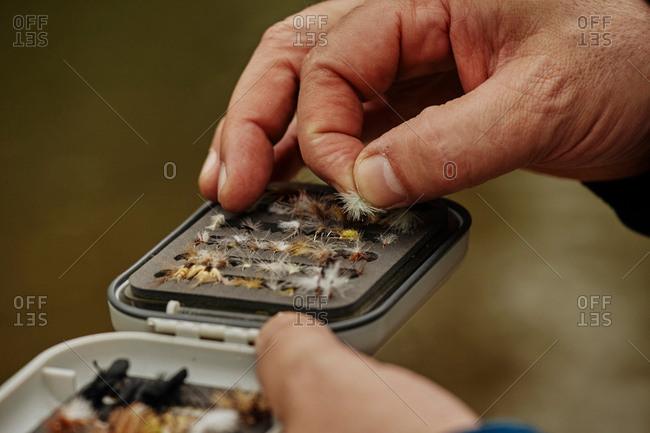 Man selecting fishing fly from storage container, close-up