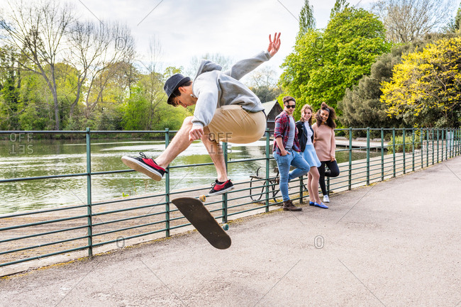 Young male skateboarder doing jump trick for friends in Battersea Park