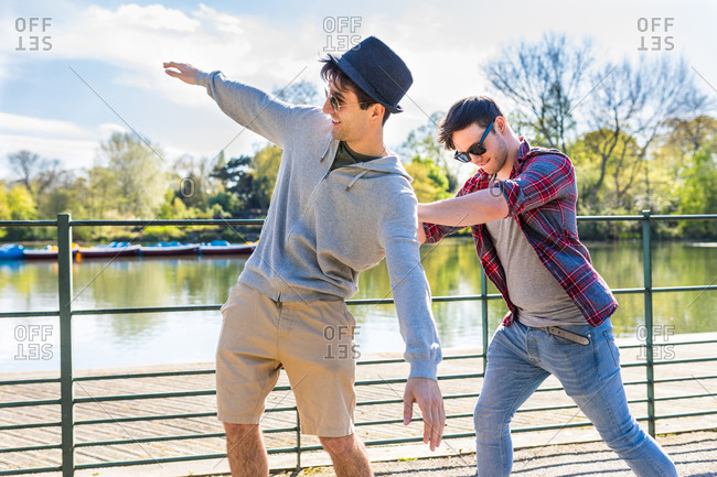 Young man pushing friend on skateboard in Battersea Park