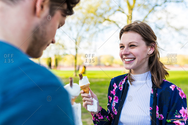 Young couple eating ice cream cones in Battersea Park