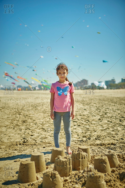 Portrait of young girl standing behind sand castles on beach, Rimini, Italy