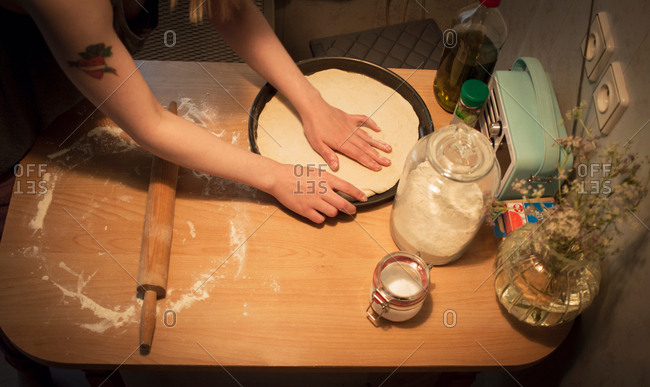 Young woman at home, making home-made pizza, mid section