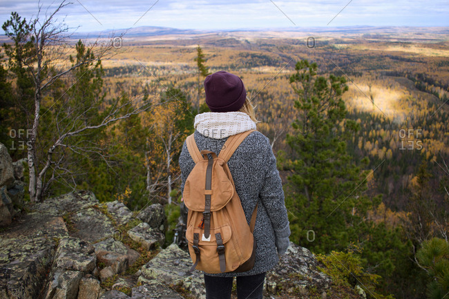Young woman standing on mountainside, looking at view, Sverdlovsk Oblast, Russia