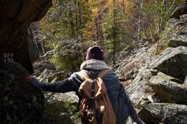 Young woman hiking, leaning on rock, rear view, Sverdlovsk Oblast, Russia
