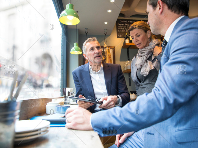 Businessmen and woman having discussion in restaurant window seat