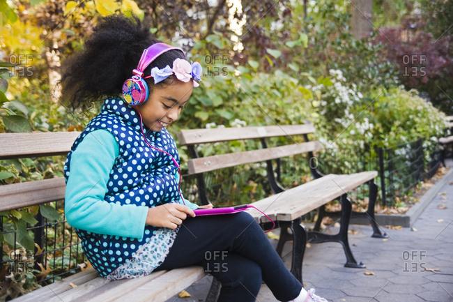 Girl sitting on park bench wearing headphones using digital tablet