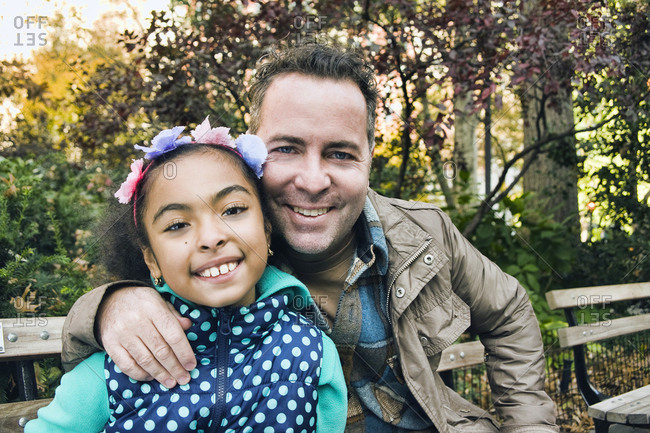 Father and daughter in park looking at camera smiling