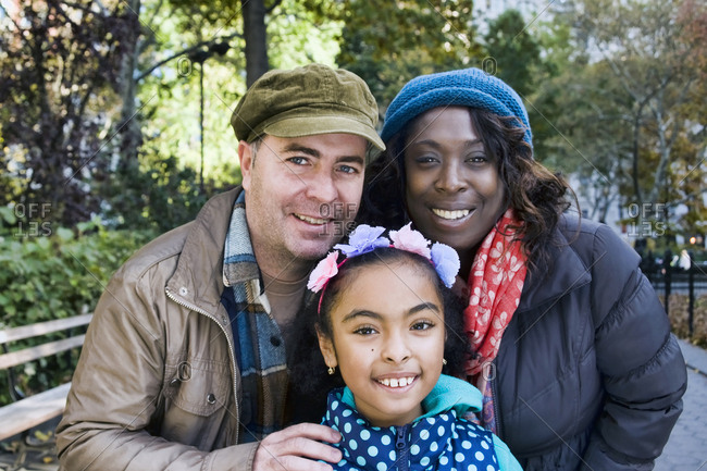 Family in park looking at camera smiling