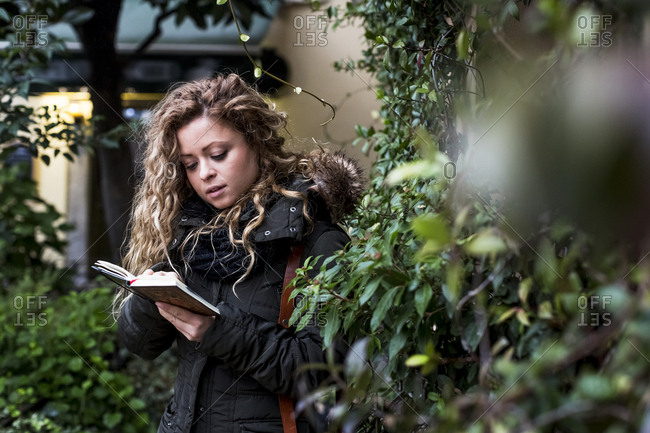 Woman in street reading book, Milan, Italy