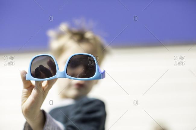 Boy holding up sunglasses