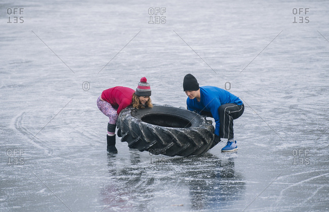 Couple flipping tire on frozen lake