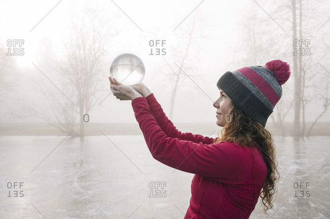 Woman holding up crystal ball on frozen lake