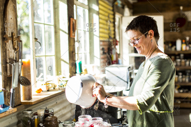 Woman pouring liquid into preserves jars in kitchen