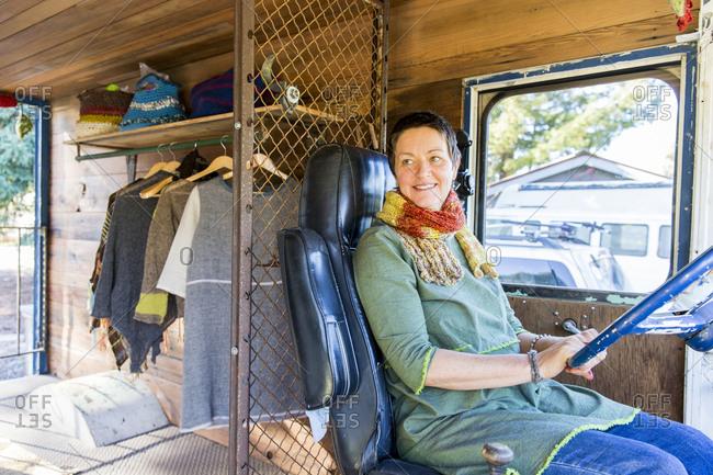 Mature hippy woman in driving seat of camper van
