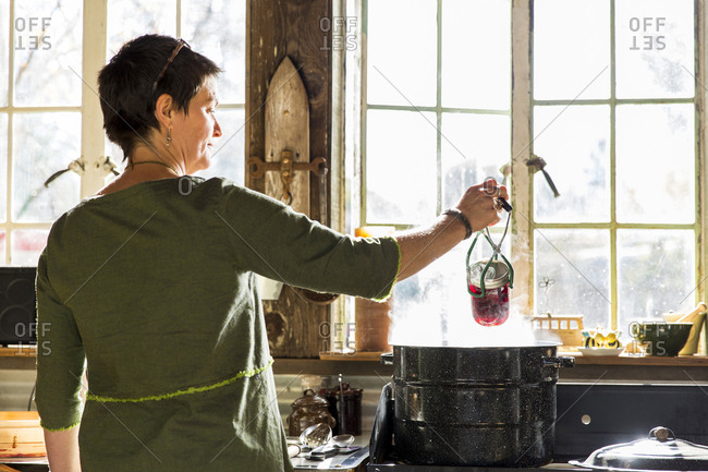 Rear view of woman removing beetroot preserves jar from steaming saucepan