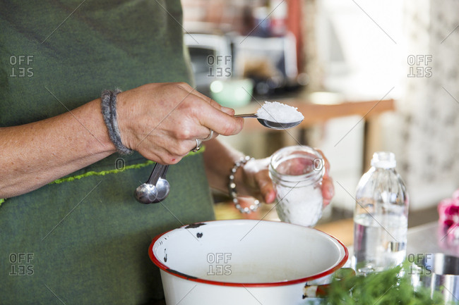 Hand of woman adding sea salt to bowl in kitchen