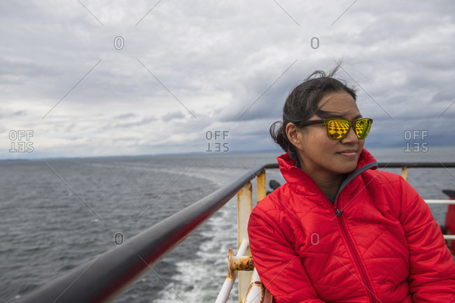 Woman sitting on ship-deck passing the Patagonian fjords, Chile