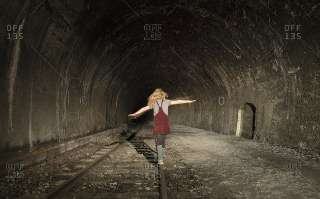 Girl in a deserted railway tunnel, walking along track, rear view