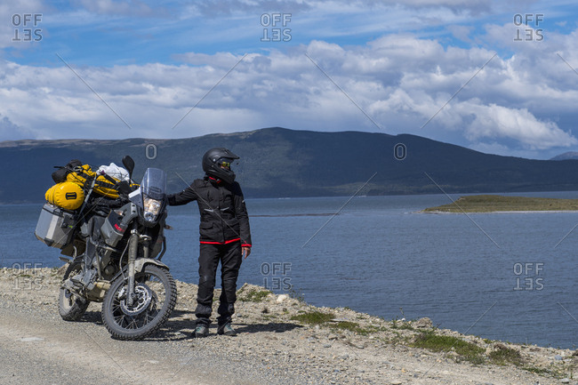 Woman standing next to her off road touring motorbike on Ruta J, Tierra del Fuego, Argentina