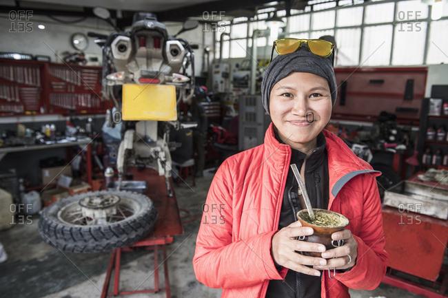 Portrait of woman drinking mate tea in motorbike mechanic's workshop, Rio Grande, Tierra del Fuego, Argentina