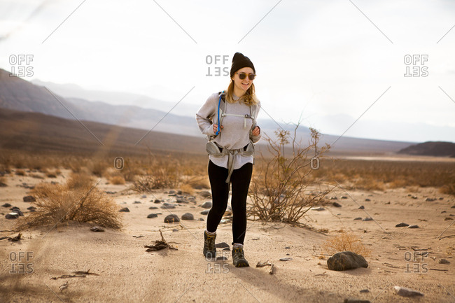 Trekker running in Death Valley National Park, California, US