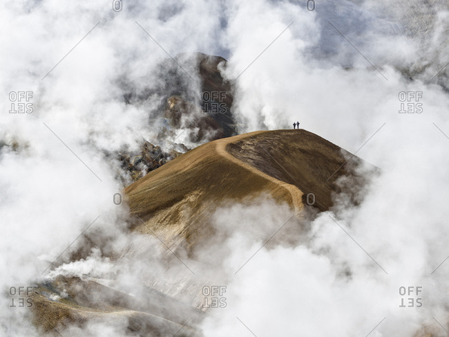 Hikers on mountain, surrounded by geothermal smoke, Kerlingarfjoll, Iceland