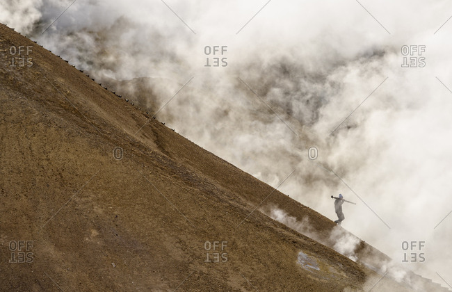 Hiker on mountain, surrounded by geothermal smoke, Kerlingarfjoll, Iceland