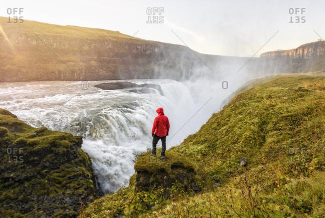 Hiker watching waterfall, Gullfoss, Iceland