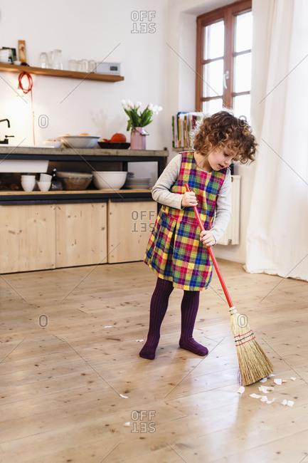 Cute girl sweeping kitchen floor