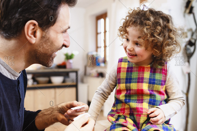 Mature man showing daughter adhesive plasters in kitchen