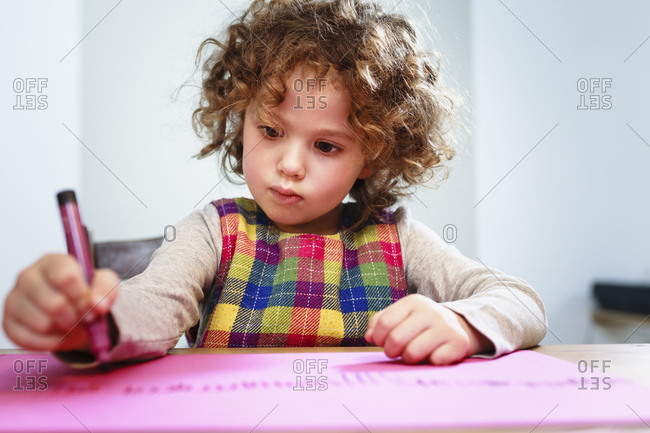 Girl drawing on pink paper at table