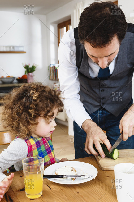 Man slicing cucumber for daughter sitting at table
