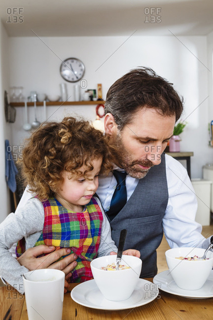 Man and daughter having cereal breakfast in kitchen