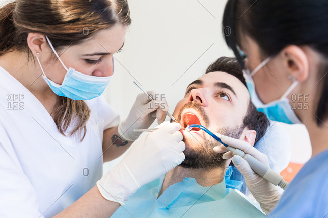 Dentist and dental nurse giving male patient dental examination