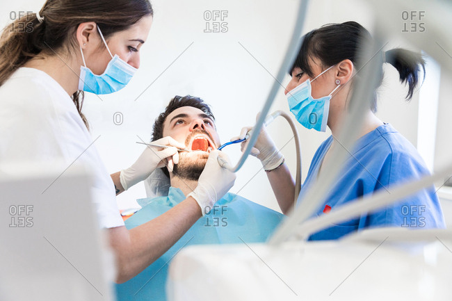 Female dentist and dental nurse using dental drill on male patient