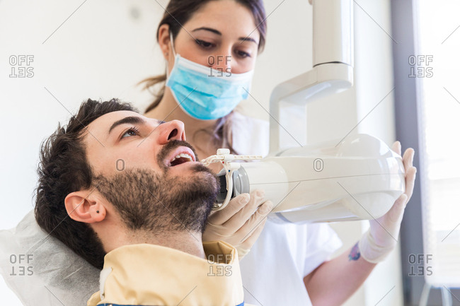 Female dentist using x-ray machine on male patient