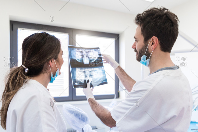 Male and female dentists analyzing x-ray in dentist office