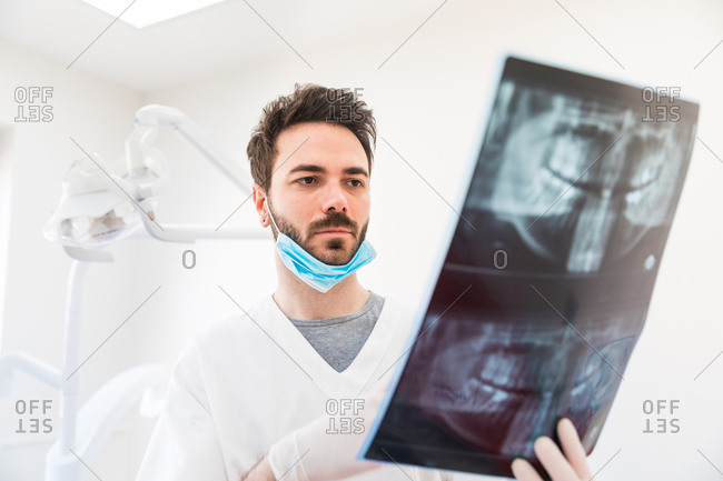 Male dentist analyzing x-ray in dentist office