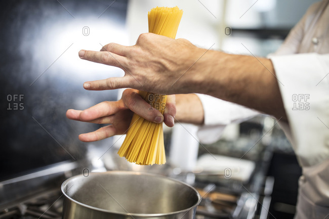 Chef putting spaghetti in saucepan on stove, close-up, overhead view
