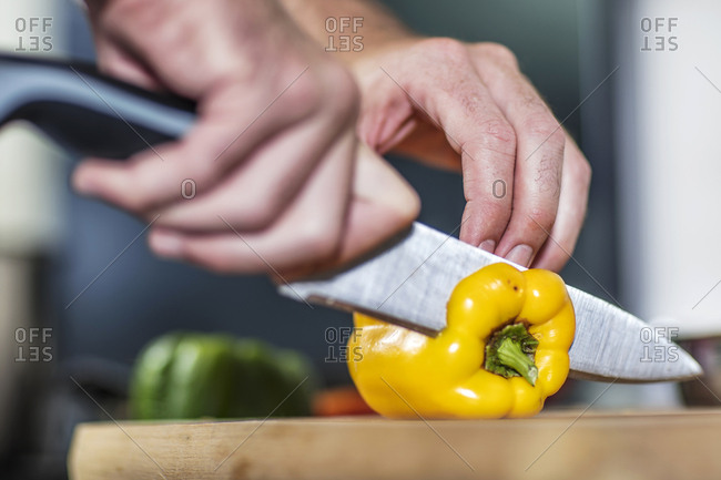 Chef slicing yellow pepper, close-up