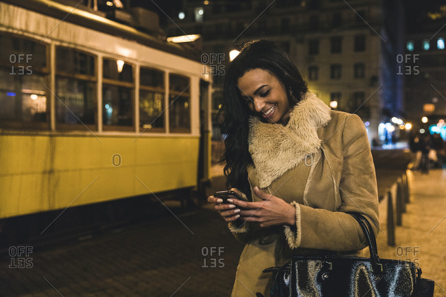 Young woman in city at night, using smartphone, Lisbon, Portugal