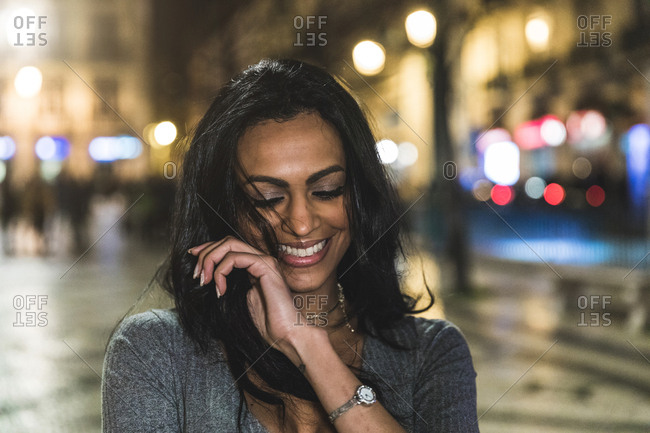 Portrait of young woman in city at night, laughing, Lisbon, Portugal