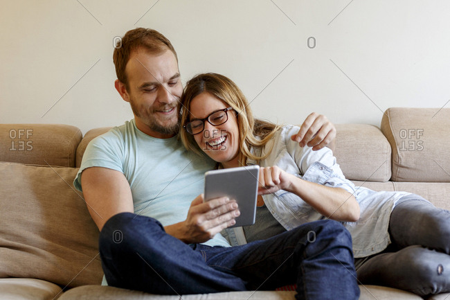 Mid adult couple relaxing on sofa, looking at digital tablet