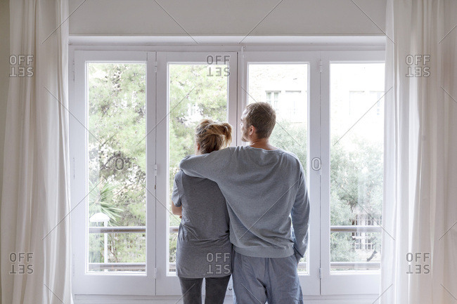 Mid adult couple at home, looking out of window, man hugging woman, rear view